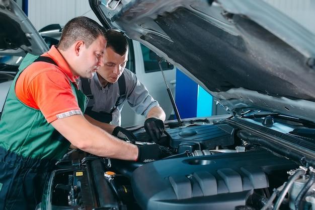 В автосервисе работают два красавца-механика в погонах. ремонт и обслуживание автомобилей. Premium Фотографии
