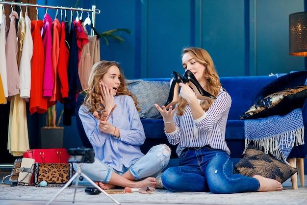 トレンドシューズを議論する2つのハンサムな若い女性。 Premium写真