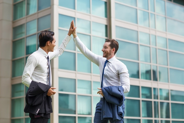 Two happy adult business men high fiving Free Photo