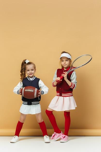 2人の幸せで美しい子供たちは、さまざまなスポーツを見せています。感情の概念。 無料写真