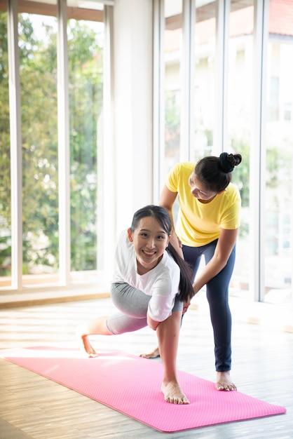 2 счастливых азиатских женщины в представлениях йоги в студии йоги с сценой установки света natura / концепцией тренировки / практикой йоги / космосом экземпляра / студией йоги Premium Фотографии