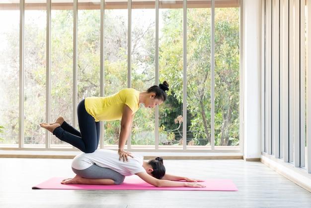 2 счастливых азиатских женщины в представлениях йоги в студии йоги с сценой установки естественного света / концепцией тренировки / практикой йоги / космосом экземпляра / студией йоги Premium Фотографии