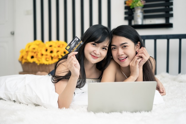 Two of happy asian young female friends surfing the internet for online shopping on a laptop and hold credit card Premium Photo