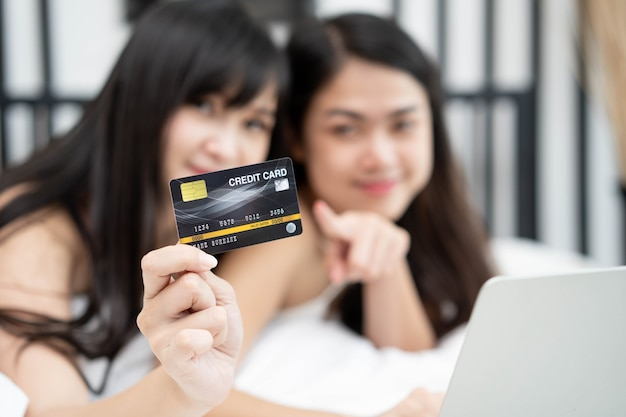 Two of happy asian young female friends surfing the internet for online shopping on a laptop and holding credit card Premium Photo