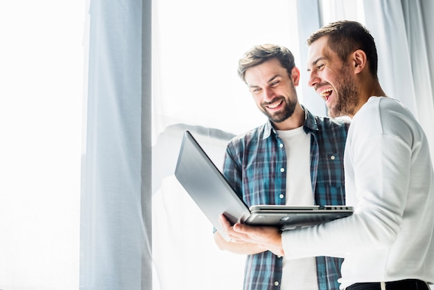 Two happy businessman working on laptop Free Photo