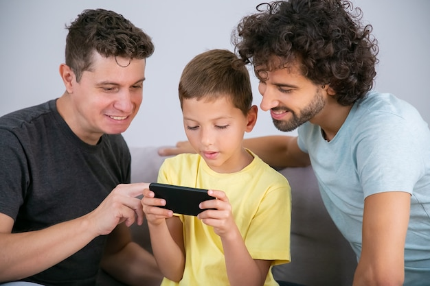 Free Photo Two Happy Dads Teaching Son To Use Online App On Cell Boy Playing Game On Mobile Phone Family At Home And Communication Concept
