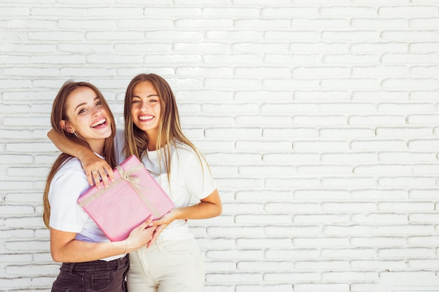 Two Happy Female Friends With Birthday Gift In Front Of Brick Wall Free Photo
