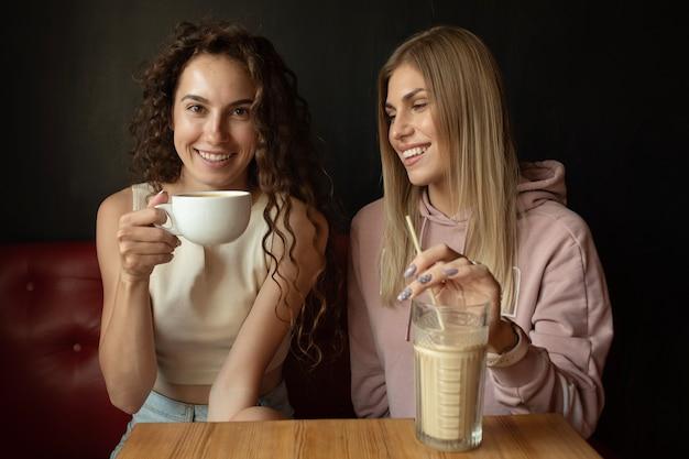 Два счастливых друга разговаривают в кафе Premium Фотографии