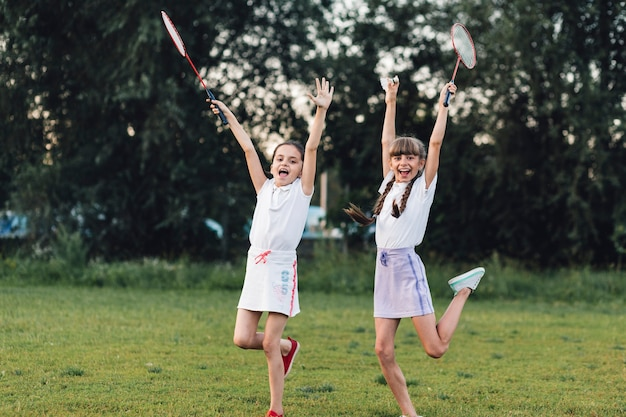 Two happy girls holding badminton jumping in the park with joy Free Photo