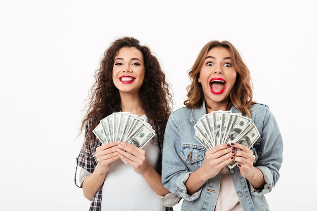 Two happy girls holding money and rejoices  over white wall Free Photo