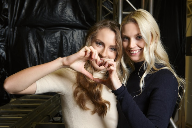Two happy girls in knitted clothes at backstage of fashion week make heart shape by her hands Premium Photo
