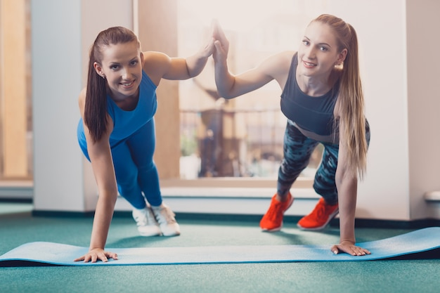 Two happy girls perform sports exercise at workout Premium Photo