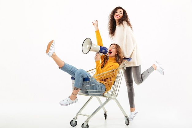 Two happy girls in sweaters having fun with shopping trolley and megaphone over white wall Free Photo