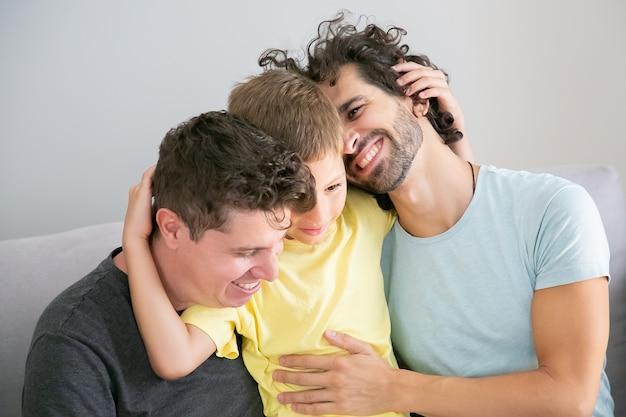 Due bei padri e figlio felici che si siedono sul divano insieme e si abbracciano. famiglia felice e concetto di genitorialità Foto Gratuite