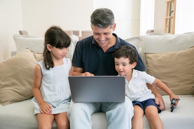 2人の幸せな子供とお父さんが自宅のソファに座ってラップトップを使用し、ディスプレイを見つめています。 無料写真
