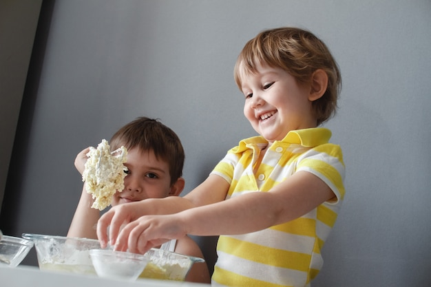Two happy little kids making shortbread .they have fun laughing and stirred the dough. Premium Photo