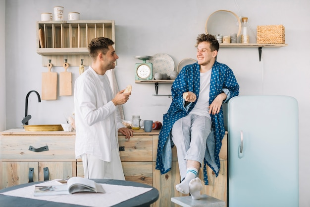 Two happy man having morning breakfast in kitchen Free Photo