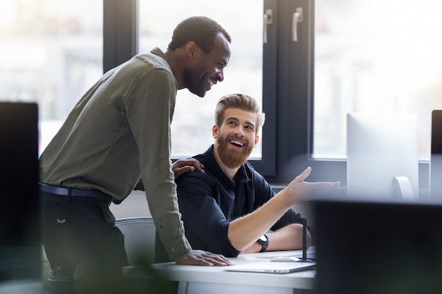Two happy men working together on a new business project Free Photo