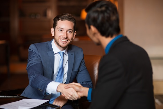 Two happy partners shaking hands in cafe Free Photo