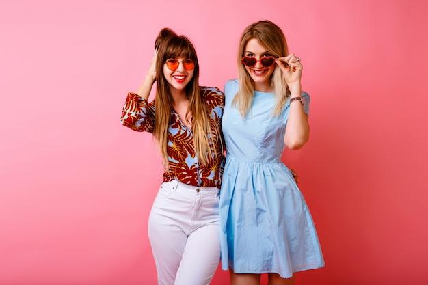 ピンクの壁で一緒に楽しんでいる2人の幸せなかわいい姉妹の親友の流行に敏感な女性、カラフルなトレンディな夏の服装、ヴィンテージの気分。 無料写真