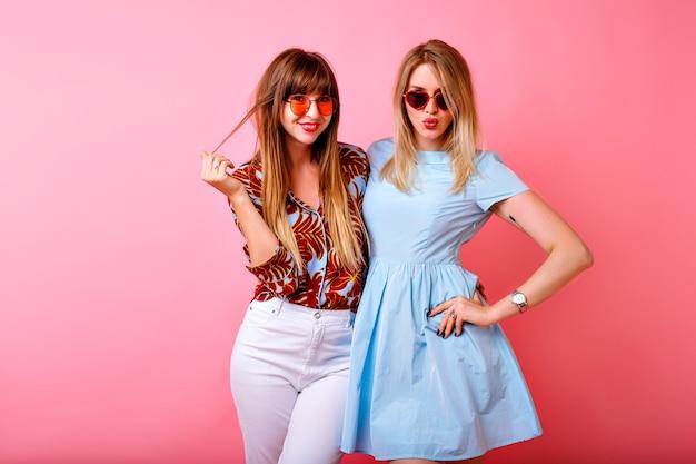 Due belle sorelle felici migliori amici hipster donne divertendosi insieme al fondo rosa dello studio Foto Gratuite