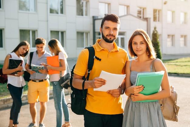 Два счастливых студентов с рюкзаками и книгами в руках, улыбаясь на камеру Бесплатные Фотографии
