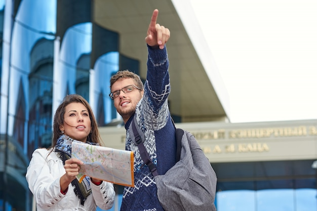 Two happy tourists couple searching location together with a phone and map and pointing with the fin