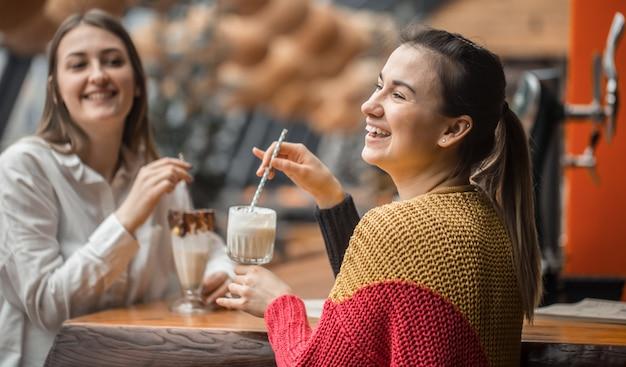 2人の幸せな女性がカフェに座って、ミルクセーキを飲んでいます。 無料写真
