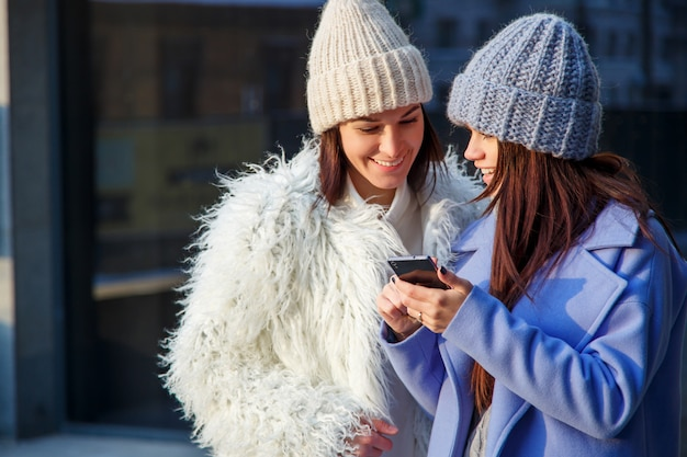 Two happy women friends sharing social media in a smart phone outdoors Premium Photo