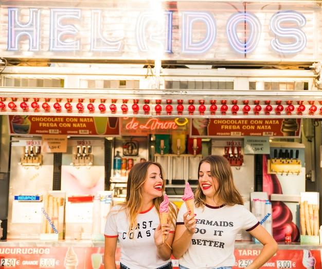 Two happy women holding ice cream at amusement park Free Photo