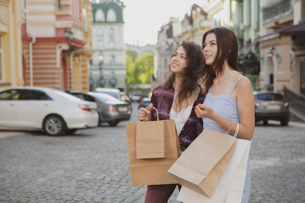 Two happy women sightseeing together after shopping on their vacation Premium Photo