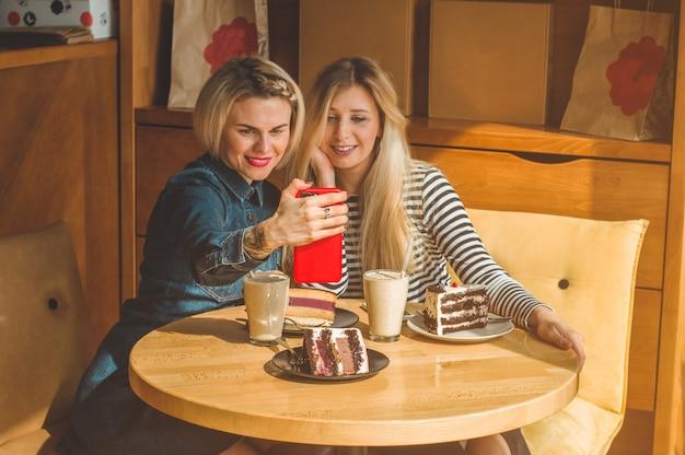 Две счастливые женщины сидят в кафе и делают селфи по телефону, пьют коктейль, рассказывают друг другу забавные истории, находясь в хорошем настроении, счастливо смеясь. лучшие друзья Premium Фотографии