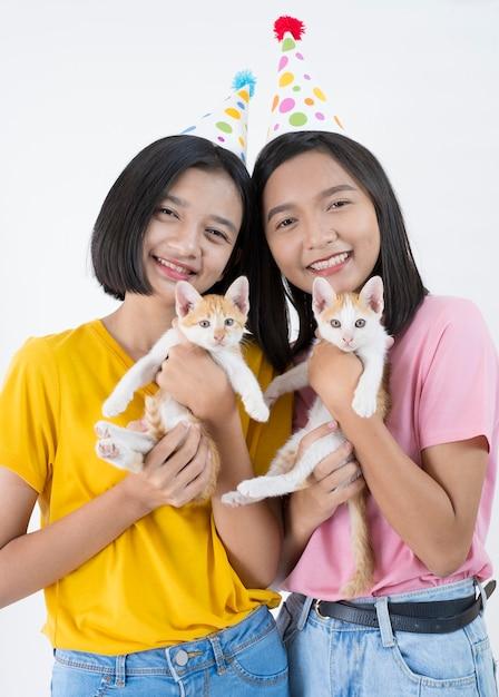두 행복 한 어린 소녀는 두 고양이와 분홍색과 노란색 셔츠와 파티 모자를 착용 프리미엄 사진