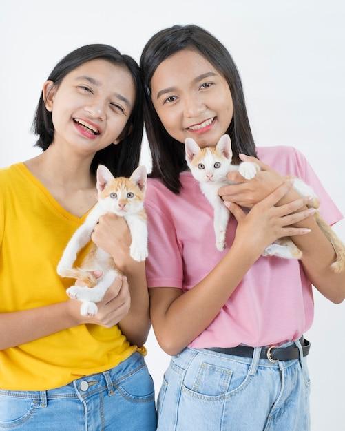 2匹の幸せな少女は2匹の猫とピンクと黄色のシャツを着ています Premium写真