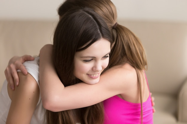 Two happy young women hugging when meeting Free Photo