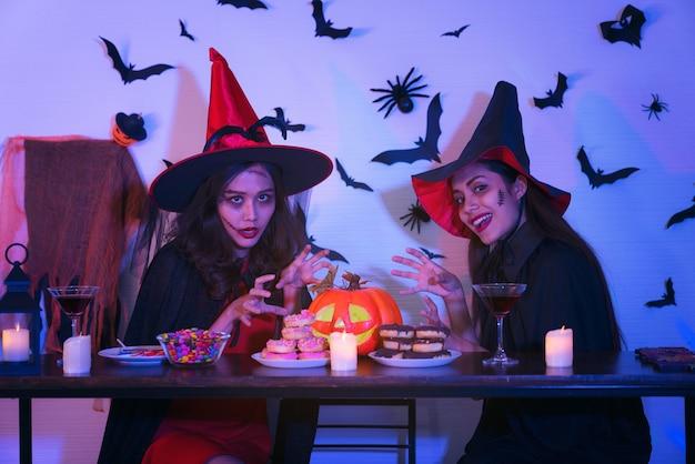 Две счастливые молодые женщины в костюмах черной ведьмы на хэллоуин на вечеринке с тыквой и коктейлями Premium Фотографии