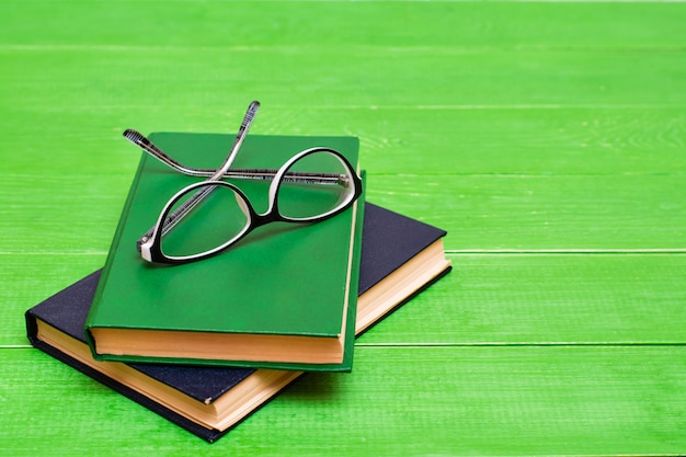 Two hardcover books and glasses  on a green wooden table. copy space Premium Photo