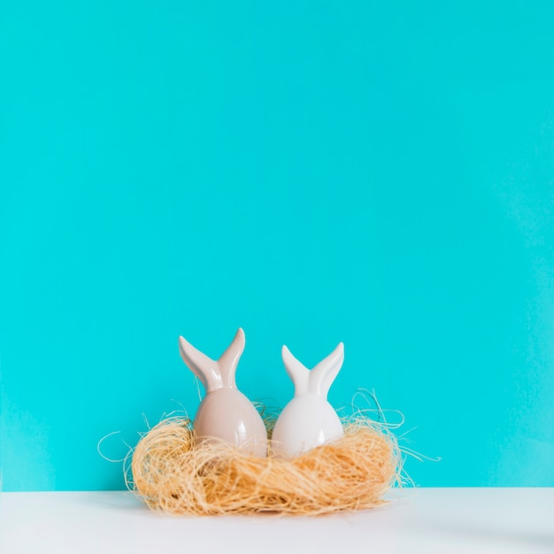 Two hare figurines in nest Free Photo