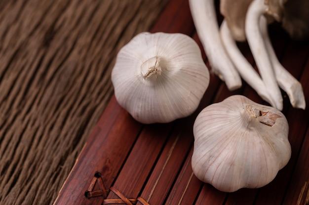 Две головки чеснока на деревянных планках и сказочный гриб Бесплатные Фотографии