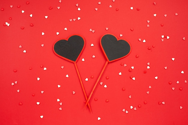 Two hearts blackboard shaped over red festive background Premium Photo
