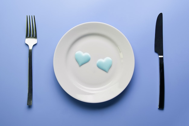 Two hearts in plate with cutlery. Premium Photo