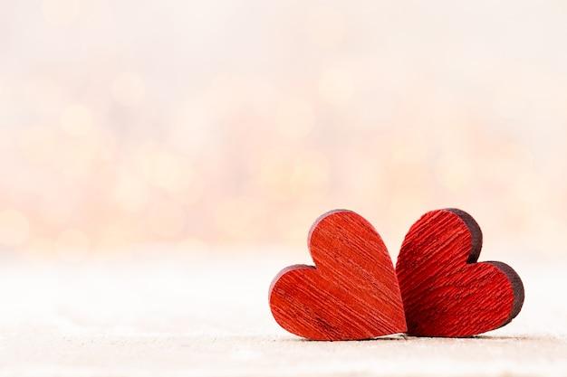 二つの心臓。背景のボケ味とバレンタインの日グリーティングカード。 Premium写真