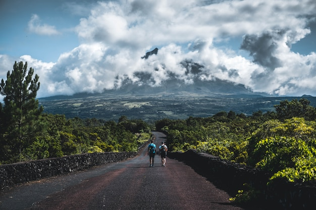 Two hikers walking on a narrow road surrounded with greenery with cloudy mountain Free Photo
