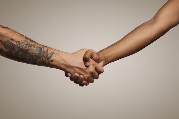 Due giovani alla moda si stringono la mano isolati su bianco Foto Gratuite