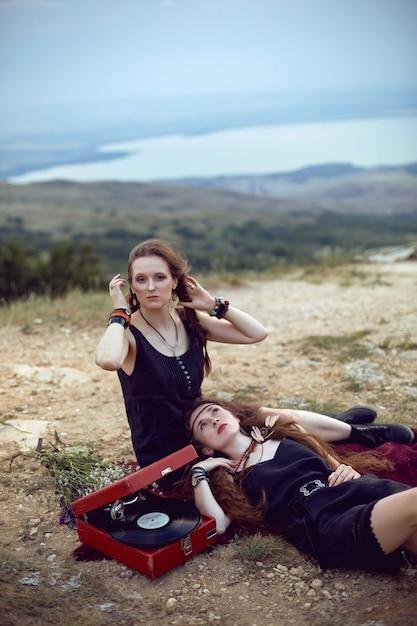 Две женщины-хиппи лежат в поле на горе со старым граммофоном на виниловой пластинке Premium Фотографии