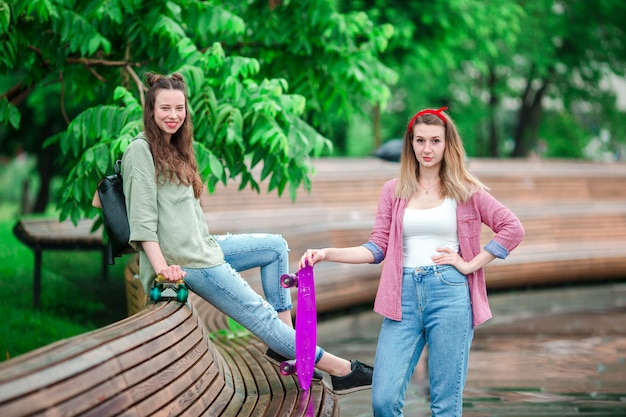 Two hipster girls with skateboard outdoors in the park. active sporty women having fun together in skate park. Premium Photo