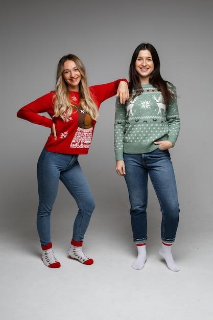 두 즐거운 긴 머리 여자 친구 금발 머리와 회색 스튜디오에 포즈 따뜻한 겨울 스웨터를 입고 갈색 머리 무료 사진