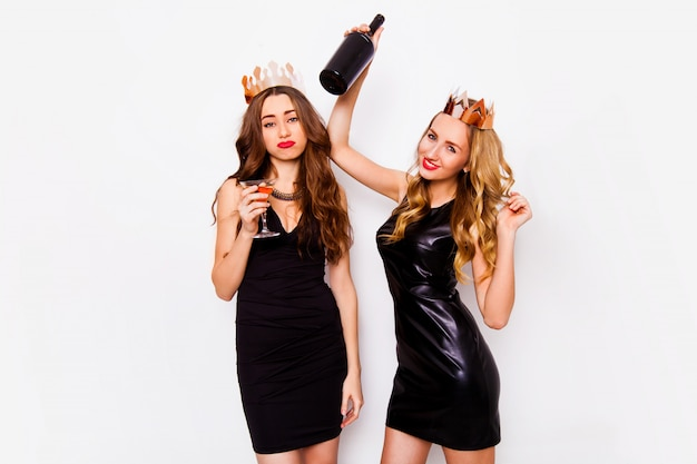 Two joyful pretty friends celebrating new year or birthday party, have fun, drink alcohol , dancing . emotional faces. elegant women posing indoor studio portrait white background. Free Photo