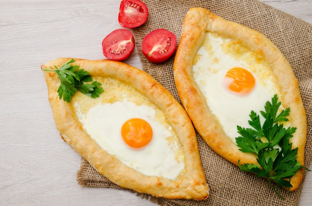 Two khachapuri with egg, parsley and tomatoes on sackcloth, top view Premium Photo
