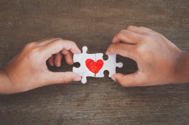 Two kid hands connecting couple jigsaw puzzle piece with drawn red heart Premium Photo